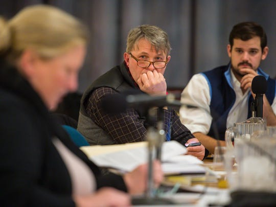 Burlington City Councilors Richard Deane, center, and Adam Roof listen to attorney Ralphine O'Rourke as the council discusses the final approval to the sale of Burlington Telecom on Wednesday, December 27, 2017.