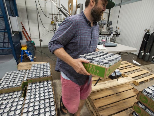 Matt Wilson stacks cans of Green State Lager at the