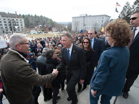 Gov. Phil Scott is greeted after signing three gun reform bills on the steps of the Statehouse in Montpelier on Wednesday , April 11, 2018.