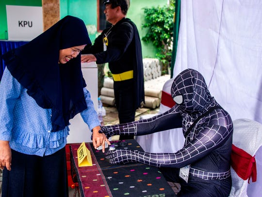 Election workers dressed in superhero costumes register