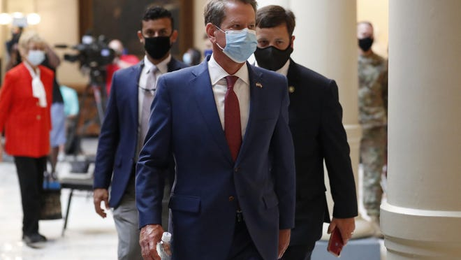 Georgia Gov. Brian Kemp returns to his office after giving a coronavirus briefing at the Capitol on July 17 in Atlanta.  Kemp has sued Atlanta over its face-mask requirement.