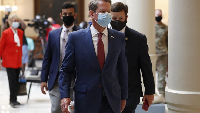 FILE - In this July 17, 2020, file photo, Georgia Gov. Brian Kemp returns to his office after giving a coronavirus briefing at the Capitol in Atlanta. Kemp says he's withdrawing a request for an emergency order that would block Atlanta from ordering people to wear masks in public or imposing other restrictions related to the COVID-19 pandemic.