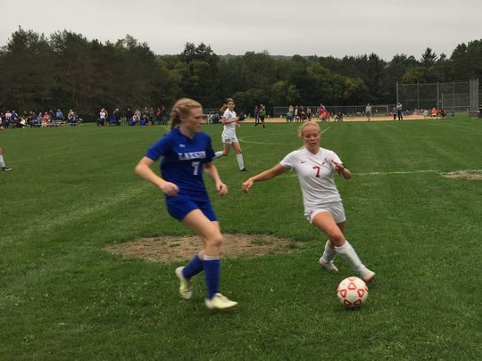 Groton's Taylor Thompson, right, battles for the ball with Lansing's Megan Dean on Friday.