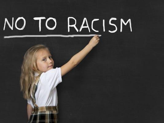 junior schoolgirl writing no to racism in school classroom blackboard