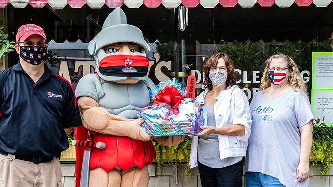 From left to right: Nathan Black, ESU's manager of environmental health and safety and ESU's Warrior mascot present Kathy Rodgers and staff member Trish Campanella with a gift basket. Rodgers made the mask worn by the mascot.