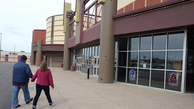 Branden Balkovic, 37, of Bradford, and his wife,; Jolene Balkovic, 33, walk to the entrance March 14, at Cinemark's Tinseltown theater. The Summit Township business will reopen Aug. 21.