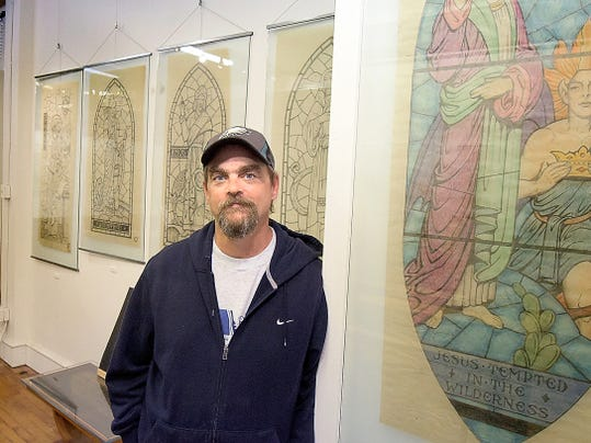 Rudy Art Glass co-owner Matt Mitchell poses with historic stained-glass renderings at the Rudy Collective Gallery in York City on Friday. The company will host an open house Saturday, Oct. 17, from noon to 5 p.m. Bill Kalina - bkalina@yorkdispatch.com
