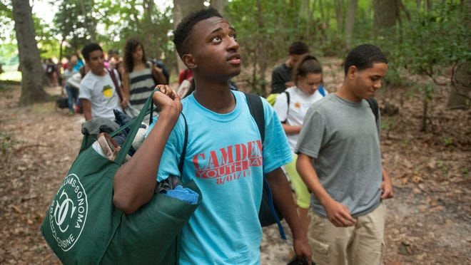 17-year-old Rudy Underdue of Camden. front, a member of the Lifting Up Camden's Youth program takes in the surroundings as he and other Lifting Up Camden's Youth program members carry their belongings to their sleeping quarters shortly after arriving to the Pine Hill Scout Reservation, where they will be camping over the weekend.   01.01.14