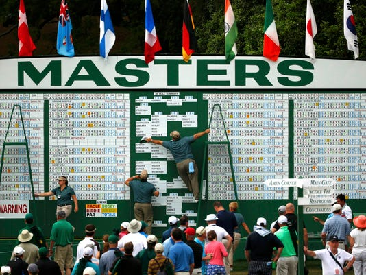 Golf patrons watch the main Masters scoreboard as workers perform updates during second round play of the Masters golf tournament at the Augusta National Golf Course in Augusta