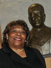 Wilma Mishoe stands with a bust of her father, Luna, who was president of Delaware State College from 1960 to 1987.