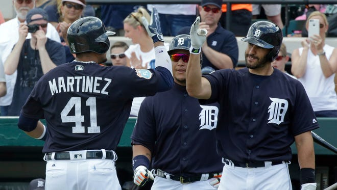 After hitting a home run in the first inning against the New York Yankees, the Detroit Tigers' Victor Martinez (41) is greeted by teammates Miguel Cabrera, center, and J.D. Martinez in a spring training game Thursday, March 31, 2016, in Lakeland, Fla.