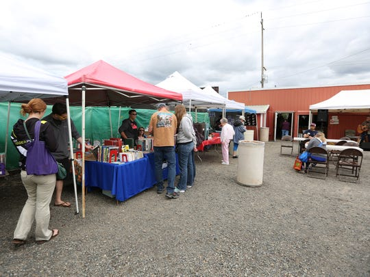 Customers browse the offerings on Saturday, June 11, 2016, during the Salem Public Market's annual Strawberry Festival.