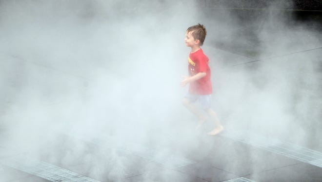 Noah Arebalo, 3, of Erlanger dashes through a mist fountain in Smale Park. A section of the park west of the bridge is now open.