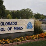 In this Oct. 2, 2015 photo, a student walks past the entrance to the Colorado School of Mines, a public research university devoted to engineering and applied science, in Golden. A graduate of Colorado School of Mines who wanted to cite Bible verses on a football locker-room nameplate for a donation he made is suing his alma mater for rejecting his request.