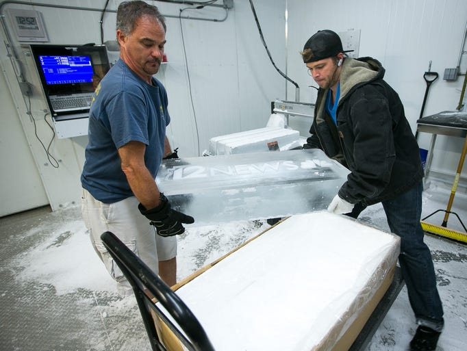 Owner Mark Armitage, left, and Matthew Novak pick up ice for the custom 12 News desk at Armitage Ice in Phoenix on Wednesday, July 23, 2014.