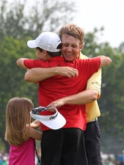 David Toms hugs his son, Carter, as daughter, Anna, waits on the 18th green after winning the 2011 Crowne Plaza Invitational at Colonial Country Club in Fort Worth, Texas. The victory is the most recent of Toms' 13 PGA Tour titles.