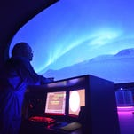 Rick Evans, Director of the W. A. Gayle Planetarium, looks on as a video shows on the ceiling during the re-opening on Thursday, March 6, 2014, in Montgomery, Ala.