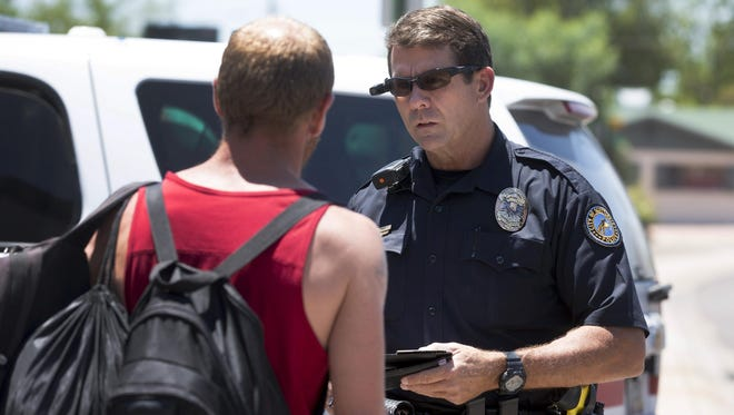 Scottsdale police Officer Don Dittman wears a body camera mounted on his sunglasses, which he activated before he made contact with a pedestrian who he said crossed the street against a red light. Some question the limitations of the technology, but the department is seeking to expand its program.