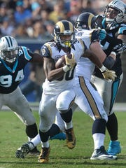 Rams running back Todd Gurley (center) carries the ball as Panthers Kony Ealy (94) (left) can only watch.