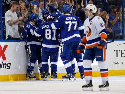 New York Islanders' John Tavares, right, skates past as the Tampa Bay Lightning celebrate a goal during the third period of an NHL hockey game Friday, March 25, 2016, in Tampa, Fla. The Lightning won 7-4. (AP Photo/Mike Carlson)