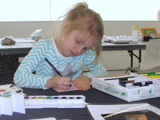 Genevieve Roddy, 6, of Lexington, South Carolina, works on a National Library Week project Monday at the Corning Museum of Glass.