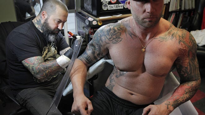 "LoveHate Tattoo owner Joseph ""Jet"" DiProjetto, left, works on customer Anthony Caruso in his shop on Alexander Street in the city. DiProjetto wanted to open a second location in Schoen Place in Pittsford, but was denied because the tattoo artists don't work out of an ""artists studio."""