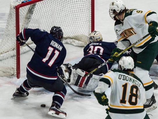 UConn goalie Adam Huska looks to the net along with