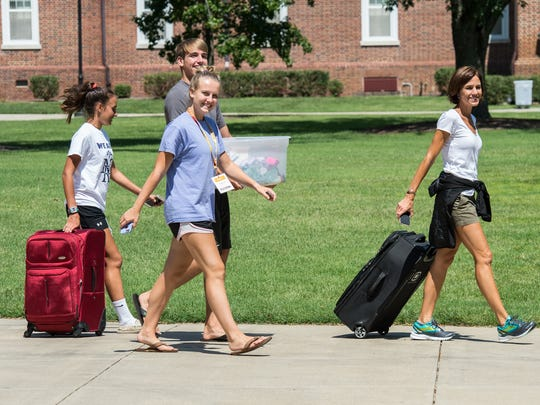 Students carry bags to their dormitories during Salisbury University's move in day on Thursday, Aug. 24, 2017.