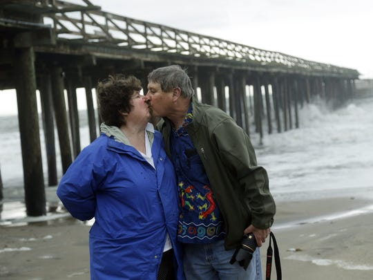 Ray Matteis, right, and his wife Penny kiss at Seacliff State Beach in Aptos, Calif.