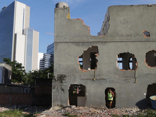 A former resident walks out of a partially demolished