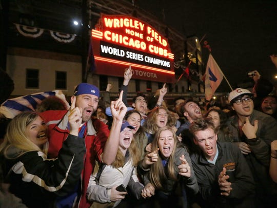 Chicago Cubs fans celebrate in front of Wrigley Field