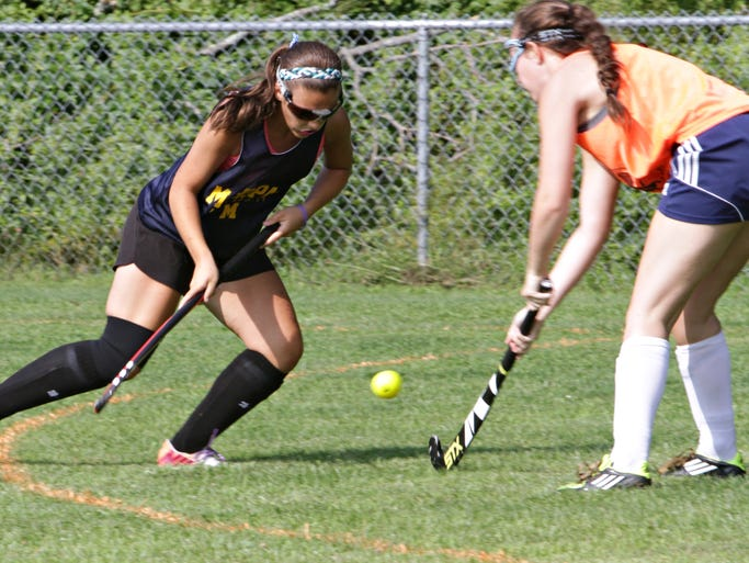 Mikaela DiBello, left, drives against a defender during the Mahopac varsity field hockey team work out Aug. 20, 2014 at Mahopac Falls Elementary School.
