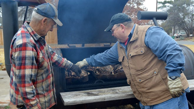 James Schmoker (left) and Billy Goins check the progress of several turkeys being smoked in preparation for the 31st annual Christmas Day Holiday Meal.