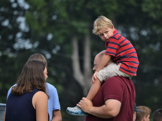 Ryan Powers, 4, sits atop his father's shoulders and