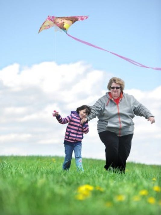 Katy Hartman holds onto her mother, Lara's hand, as the duo fly a kite on the hill last year next to the Markets at Shrewsbury (Photo by Jason Plotkin).