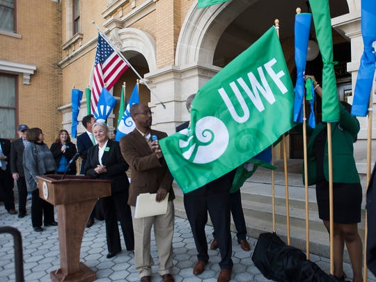 University of West Florida President Martha Saunders, center, looks on as Escambia County Commissioner Luman May helps to unveil the university's new flag as UWF and local government officials gather on the steps of the T.T. Wentworth, Jr. Florida State Museum during UWF's first Founders Week celebration.