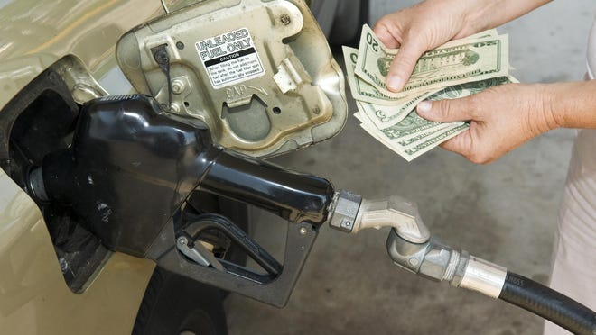 Horizontal shot of someone's hands holding money at the gas pump