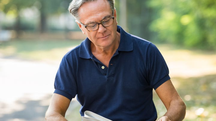 Older man reading newspaper outdoors