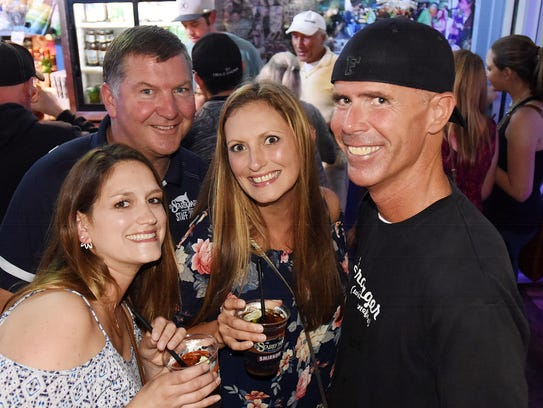 "Laura Balback, Jenn Simon and Eric Feazel have a photo taken as Steve ""Monty"" Montgomery co-owner of The Starboard in Dewey Beach works the bar (and crowd) last weekend."