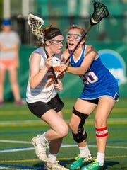 Middlebury's Satchel McLaughlin, left, drives on Mt. Anthony's Monroe Ports during the Division I girls lacrosse high school state championship  on Monday, June 12, 2017.