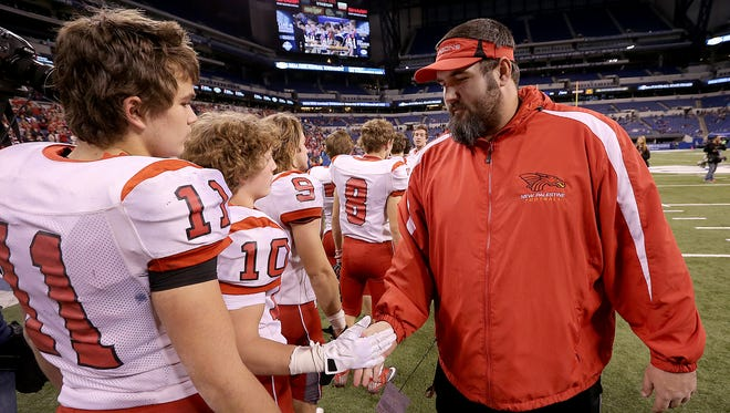New Palestine's Kyle Ralph congratulates his players after defeating the New Prairie Cougars.The New Palestine Dragons defeated the New Prairie Cougars 77-42 in the IHSAA Class 4A State Football Championship game Friday, November 28, 2014, afternoon at Lucas Oil Stadium.