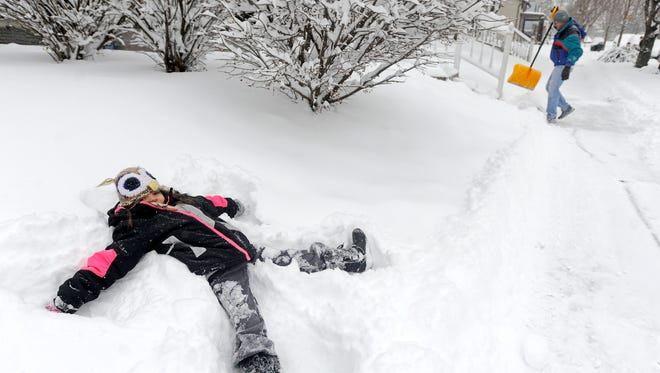 Aurora Graves, 6, makes a snow angel in her front yard on Thursday after the snow storm as her parents shovel snow off their sidewalk and clean off their car. Aurora told the Gazette her favorite part of the snow day was getting to make snow angels.
