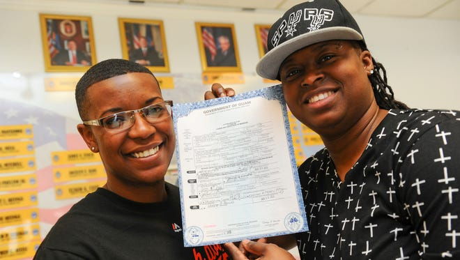 Deasia Johnson, left, and Nikki Dismuke hold up their marriage license after they were married at the Department of Public Health and Social Services in Mangilao, Guam, on June 9. They were the first gay couple to marry in Guam.