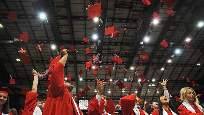 Lincoln High School graduates throw their caps in the air at the end of the Lincoln High School commencement ceremony Sunday, June 5, 2016, at the Sioux Falls Arena in Sioux Falls.