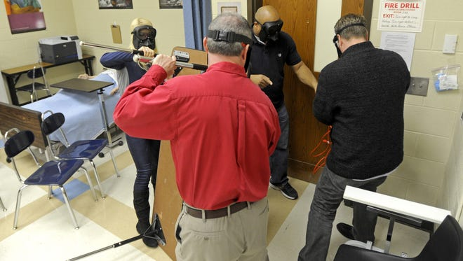 Teachers and other adult attendees attempt to barricade a classroom door with tables and chairs during a 2015 active shooter training session at Chillicothe High School led by a trainer from the ALICE Training Institute. School safety training grants recently announced for all local school districts can be used for such things as training for school resource officers, safety and security materials and programs to identify and help students struggling with mental health issues.