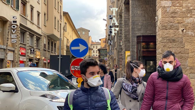 People walking the streets of Florence, Italy, wear face masks in an effort to avoid coronavirus.