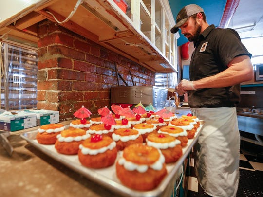Ian Carleton, lead baker at Hurts Donut in downtown Springfield, decorates pineapple upside down doughnuts on Monday, November 28, 2016.