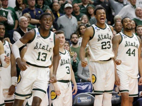 Michigan State starters including Xavier Tillman (23) and Nick Ward (44) cheer their bench players in the last seconds of a second round men' s college basketball game against Minnesota in the NCAA Tournament, in Des Moines, Iowa, Saturday, March 23, 2019. Michigan State won 70-50. (AP Photo/Nati Harnik)