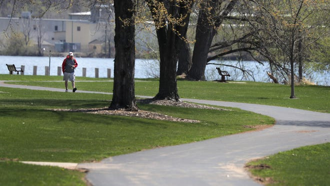 Chad Purdy walks a trail Monday after fishing along the Fox River at Island Park.