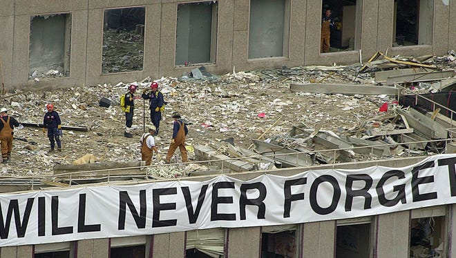 Firefighters and rescue workers looking through rubble, Thursday, Sept. 27, 2001, on a roof of the World Financial Center located across the street from the area where the World Trade Center once stood.